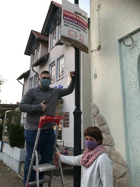 Das Foto zeigt Iris Wetzel und Justin Köhler bei der Plakataktion in Calden am letzten Donnerstag